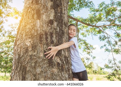 Young asian girl hugging tree trunk in park , environment protection concept.