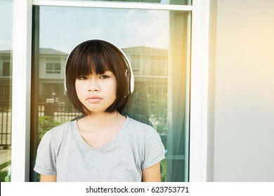 Young asian girl listen music with headphones at home.