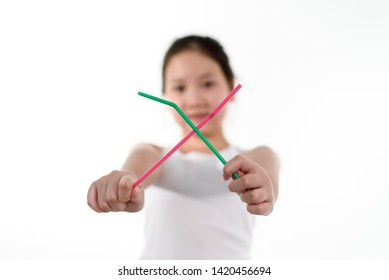 Young Asian girl make symbal against to use plastic straw that will create garbage and pollution.