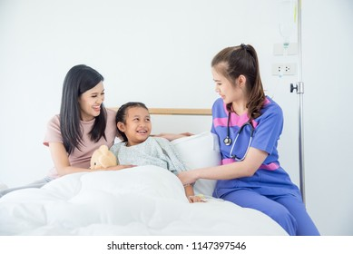 Young asian girl patient and mother smiling while doctor come to visit