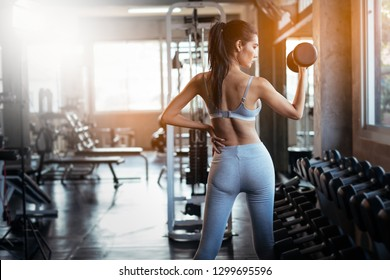 Young asian girl playing dumbbell to exercise in fitness.Slim girl lifts heavy dumbbell while training in the gym. Sports concept fat burning and a healthy lifestyle.