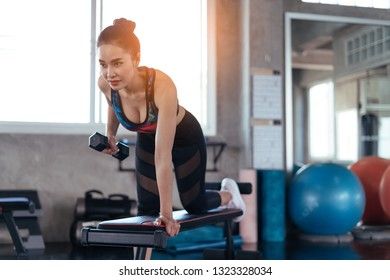 Young asian girl playing dumbbell to exercise in fitness.Slim woman lifts heavy dumbbell while training in the gym. Sports concept fat burning and a healthy lifestyle.
