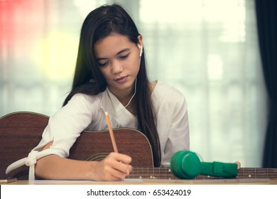 Young Asian girl playing guitar and write note on paper look like a music composer, song writer