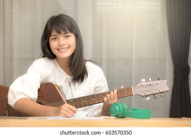 Young Asian girl playing guitar and try to be music composer, song writer