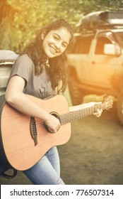 young asian girl playing guitar in garden on happy time