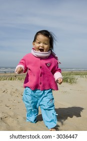 Young Asian girl playing on the beach.