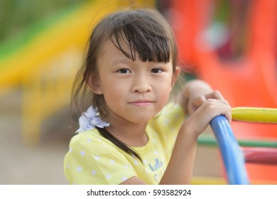 Young asian girl playing in playground.