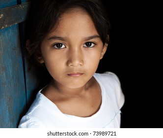 Young Asian girl portrait - child from Philippines against blue door and black background.