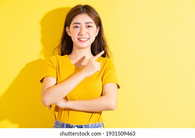 Young Asian girl posing on yellow background