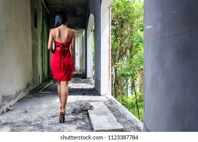 Young asian girl in red dress walking away in abandoned building