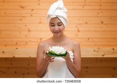 Young asian girl relax, holding a lotus in sauna cabin
