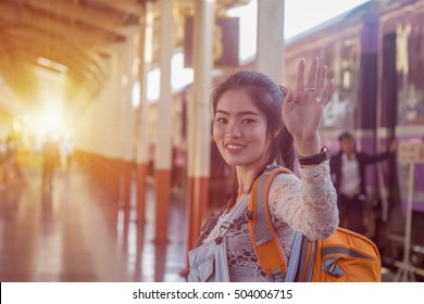 Young Asian girl say goodbye at train station before journey. Young Asian girl sent hand sign to goodbye.