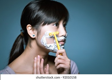 A young Asian girl shaving in a funny role reversal.