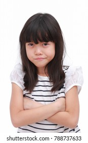 Young asian girl shows angry face and crossed her arms. Put on a black white T-shirt. Portrait image on isolate white background.