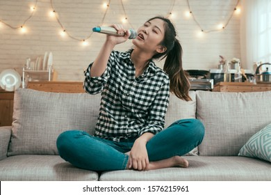 young asian girl singing with microphone on sofa at home kitchen. beautiful lady love music enjoy karaoke relax in couch in apartment. chinese female having fun alone in modern house interior.