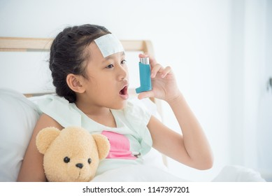 Young asian girl sitting on bed and using broncodilator inhaler for relieve asthma symptom