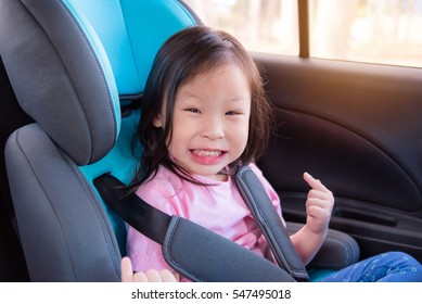 Young asian girl smiling on the car with safety belt