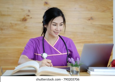 Young Asian girl, student of medicine using laptop and researching books at desk.