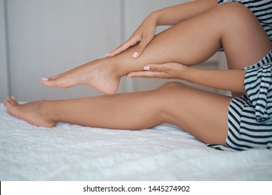 Young asian girl suffering from pain in leg at home. woman massages her legs to relieve pain