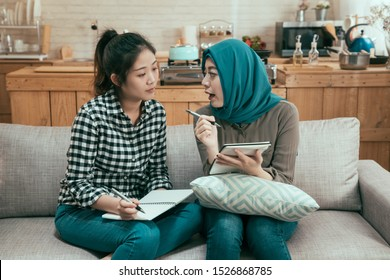 young asian girl team work partners discussing and making notes on sofa at college campus. muslim and chinese students studying together sitting on couch in dormitory. female roommates talking.