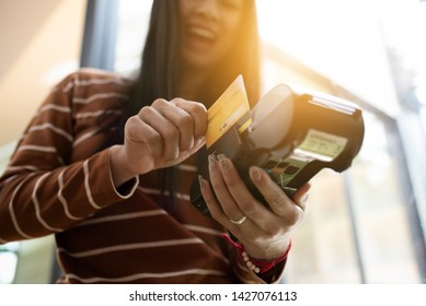 Young asian girl using credit card make a payment via payment terminal machine.