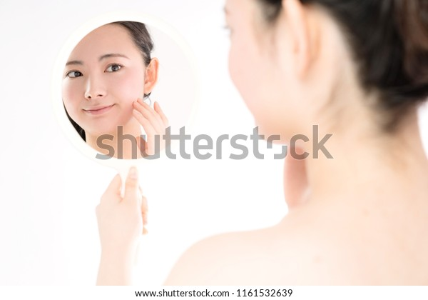 Young asian girl using a hand mirror. Skin care concept.