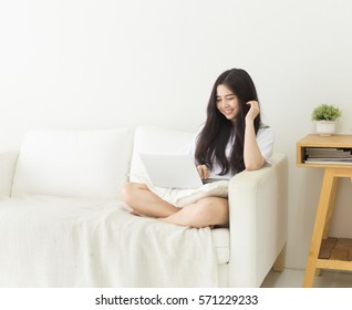 Young Asian girl using laptop on the couch with smiley face