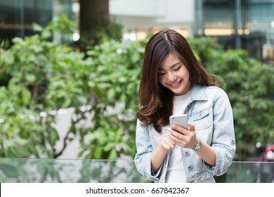 Young Asian Girl using smart phone in the garden