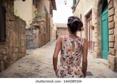 Young asian girl walking in Monticchiello town on summer day. Amazing promenade with traditional old stone houses - Tuscany, Italy, Europe