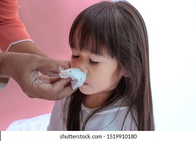 Young Asian girl wipe blood from his nose and the grandmother is hands take care