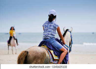 Young asian girls ridding horses on the beach.
