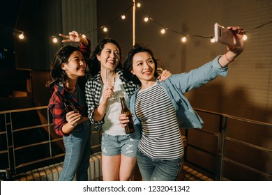 young asian girls taking self portrait on rooftop party at night. cute ladies with beers and champagne cheerfully photographing selfie by smartphone. confident women having fun enjoy time on roof.