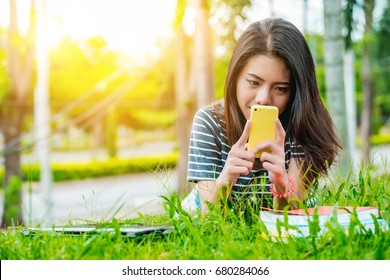 Young Asian girl/woman is reading pleasant text message on mobile phone while sitting in the park in the warm day, a gorgeous female is listening to music and searching information on cell telephone.