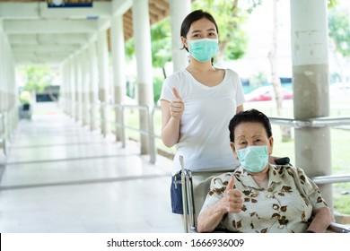 Niña asiática que cuida a su abuela sentada en silla de ruedas. La abuela, de casi 90 años, fue atendida por su nieta mientras viajaba en el parque. Gente con máscara protectora.