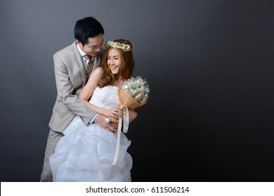 young asian groom and bride posing and smiling in studio for wedding shot.