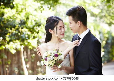 young asian groom kissing bride outdoors during wedding ceremony.