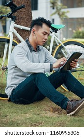 Young Asian guy browsing tablet and listening to music in earphones while sitting on ground near bicycle and tree