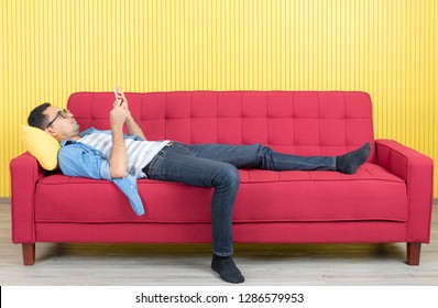 Young Asian handsome bearded man, wearing eyeglasses in denim shirt, sprawled out on red sofa, serious talking on smartphone with friend, in modern living room, bright yellow stripe wall background