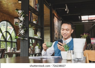 Young asian handsome business man working at the desk in coffee cafe. Talking on his smart phone. Relaxation and successful business concept.