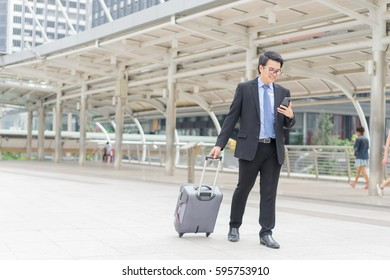 Young asian handsome businessman and glasses using smartphone while walking outside business district before work travel with suitcase and smiling at business district