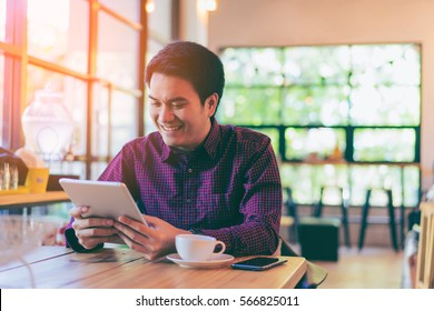 Young asian handsome businessman smiling while reading his tablet with a cup of coffee and smartphone in coffee cafe. Portrait of asian business man reading message with tablet and smart phone.