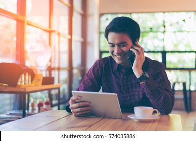 Young asian handsome businessman smiling while reading his tablet with a cup of coffee and smartphone in coffee cafe. Portrait of asian business man reading message with tablet and smart phone indoor