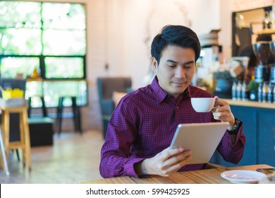 Young asian handsome businessman smiling while reading his tablet with a cup of coffee and smartphone in coffee cafe. Portrait of asian business man reading message with tablet and smart phone in shop
