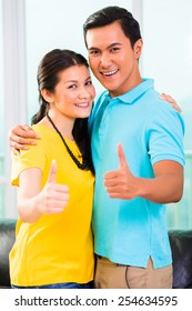 Young Asian handsome couple in apartment with city view showing thumbs up