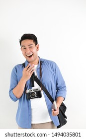 Young Asian handsome man in blue shirt and retro film camera with bag on white background travel concept