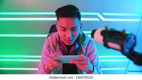 Young Asian Handsome Pro Gamer play online mobile game with smart phone and having live stream
