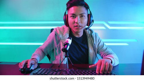 Young Asian Handsome vlogger having live stream and playing in Online Video Game