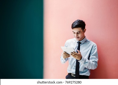 Young Asian and Happy Businessman Reading or Working on a digital Tablet at colorful wall, Social communicate Technology in Business Concept, Lifestyle of modern Male