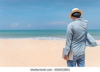 Young Asian happy man holding laptop on the beach, working outdoor in summer season, digital nomad lifestyle concepts