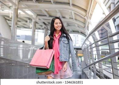 Young asian happy woman holding many bags after shopping in the city